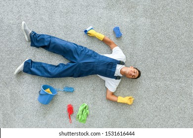 Tired young man lying on floor after cleaning flat, top view