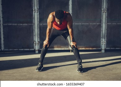 Müde junge Mann ruhen während des Trainings auf heißen Sommer in der Stadt. Atmung für Sportler mit schwarzem Fass.