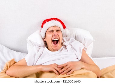 Tired Young Man in Santa Hat Yawning in the Bed at the Home
