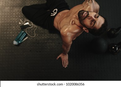 Tired young man sitting on floor and relaxing in gym after training. Male relaxing after workout session at gym.