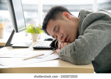 Tired young man sleeping at desk in office.  Asian businessman fell asleep on computer keyboard.