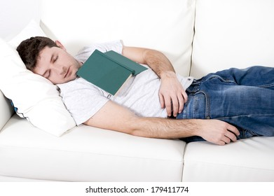 tired young man sleeping on couch with book on lap after reading