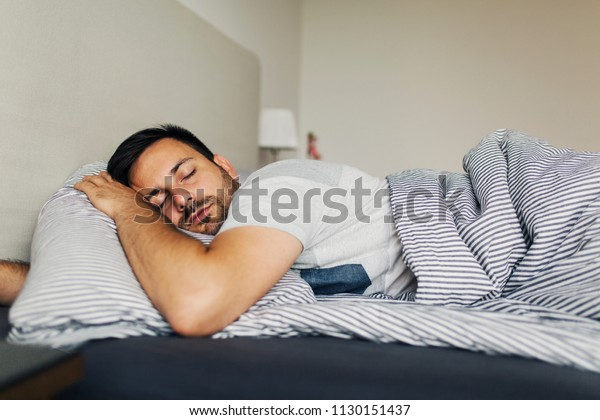 Tired young man sleeping peacefully in his bed