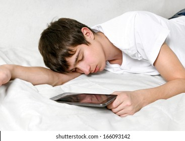 Tired Young Man Sleeps with Tablet Computer on the bed