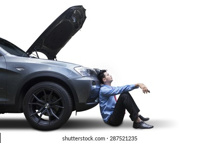 Tired young man waiting a help while sitting near the broken car, isolated on white