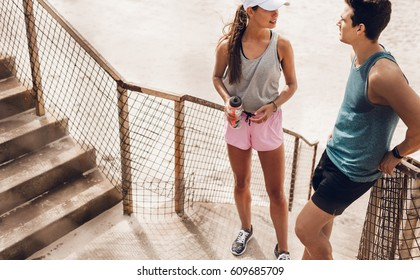 Tired young man and woman standing at beach taking break after running workout. Couple relaxing after exercising session outdoors.