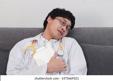 Tired young medicine Asian doctor asleep on couch at hospital