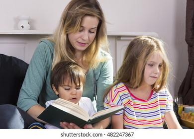 Tired young mother reading fairytale to children