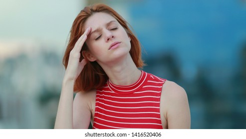 Tired young redhead woman feeling headache outside thinking deeply
