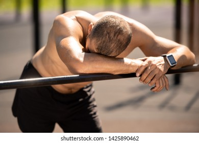 Tired young sportsman putting his arms on sports bar and keeping his head on one of them while having rest