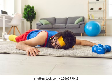 Tired young sportsman sleeping on rug after failed sports workout at home. Unmotivated lazy male athlete in glasses lying on floor after giving up fitness training with dumbbells and push-up exercises