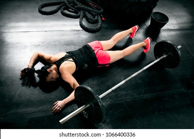 Tired young woman after hard training lying near weights