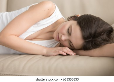 Tired young woman in casual clothing sleeping on leather soft sofa. Lady resting after hard day, fell asleep exhausted by worries and work in living room. Teenage girl lying with closed eyes, napping