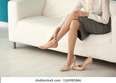 Tired young woman feeling ache in legs indoors