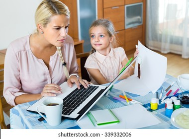 Tired young woman irritated as daughter diverts her from work at home