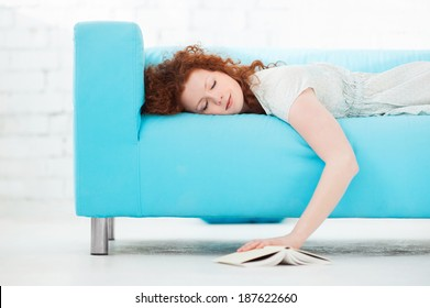 Tired young woman  lying on a sofa  at home with a book