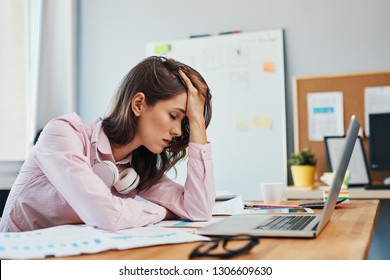 Tired young woman in office having headache working on project