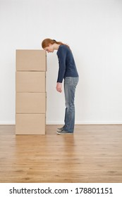 A tired young woman resting on a stack of brown storage boxes in her new home.