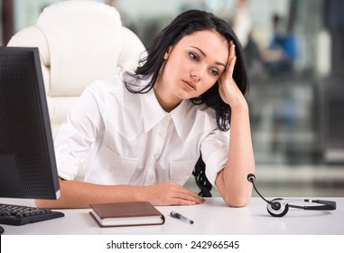 Tired young woman is sitting at the table at work in a call center.
