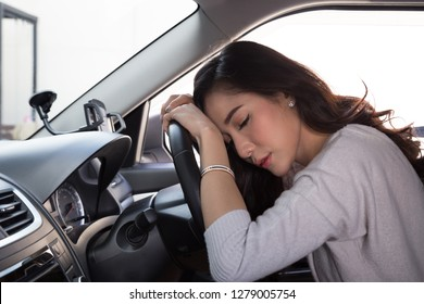Tired young woman sleep in car, Hard work causes poor health, Sit asleep while the car is on a red light, Traffic jam or overworked concept