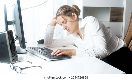Tired young woman sleeping on working desk at office