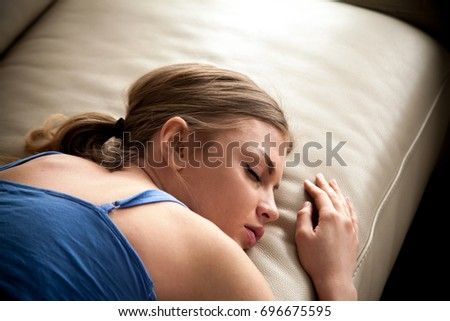 Tired young woman sleeping on couch, resting at home after busy day at work. Stressed lady falling asleep after sleepless night. Female exhausted with overwork, seeing an anxious dream or nightmare