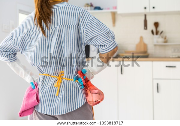 Tired young woman standing at kitchen room with cleaning products and equipment, Housework concept