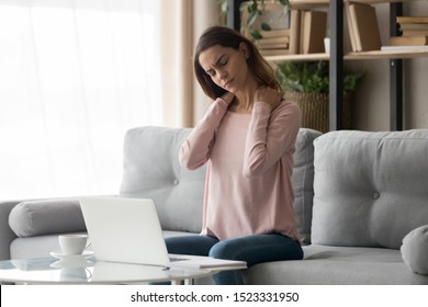 Tired young woman touch stiff neck feeling hurt joint back pain rubbing massaging tensed muscles suffer from fibromyalgia ache after long computer work study in incorrect posture sit on sofa at home