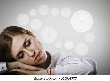 Tired young woman in white is sleeping. Sleep and Time concept. Clocks as background.