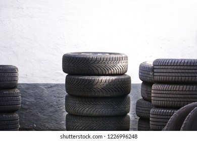Tires for sale at a tire store - stacks of old used tires.Black tire rubber, vehicle part, spare part.Pile of old worn and dirty car tires on wall background in garage.Recycle and business concept.