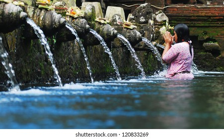 TIRTA EMPUL, INDONESIA - AUGUST 30: unidentified Woman pray and bath themselves in the sacred waters of the fountains, in Tirta Empul, Bali, Indonesia, on August 30, 2007. Fountains are in a temple