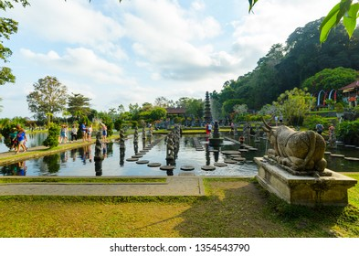 TIRTAGANGGA, INDONESIA - 28 AUG 2014: Tourists flock the Tirtagangga temple's gardens, its stone causeway and fountains, in Bali, Indonesia