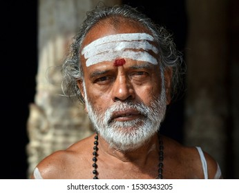 TIRUCHIRAPPALLI (TRICHY), TAMIL NADU / INDIA - FEB 6, 2016: Old Indian Shaivite Brahmin (Hindu priest who worships Shiva) with a tripundra and a red tilak mark poses for the camera, on Feb 6, 2016.