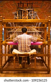 Tirunelveli, India - December 9, 2009: Rear of unidentified Indian man making traditional sari on old wooden manual handloom