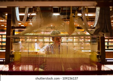 Tirunelveli, India - December 9, 2009: A unidentified Indian man, faintly visible through vertical thread weaving, making a traditional sari using a wooden handloom