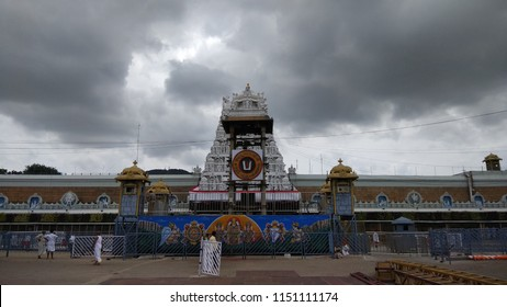 tirupati india August 6 2018: people seen walking after workship of lord venkateshwara outside tirumala temple seen with white temple tower.dark clouds in sky.mountain in background with low light.