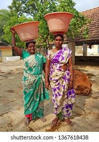 Tiruvanamalai, India - 15 december 2019: Traditional indian women with a bucket on their head working in the Ramana Ashram in Tiruvanamalai India