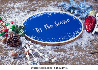 Tis The Season Written In Chalk On Blue Chalkboard Holiday Sign Background With Snow And Decorations.