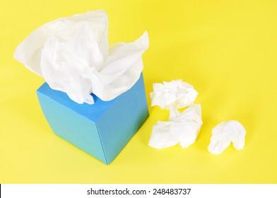 Tissue box :  Kleenex style, used tissues, yellow background.