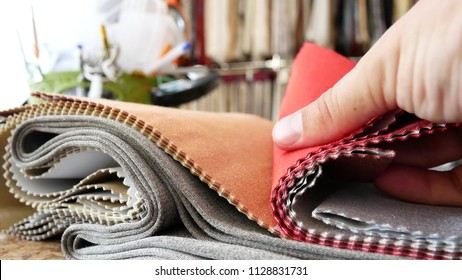 Tissue Samples, Choice of Fabrics for Upholstery. Decorator Man Leafing Through Tissue Samples. Decorator Or Tailor Touching Textile's Textures Fabric Swatches