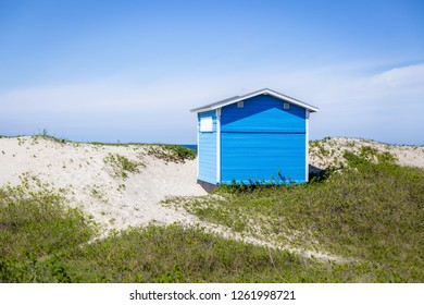 Tisvilde, Denmark - April 29, 2018: A Blue wooden beach huts in the sand dunes at Tisvilde beach