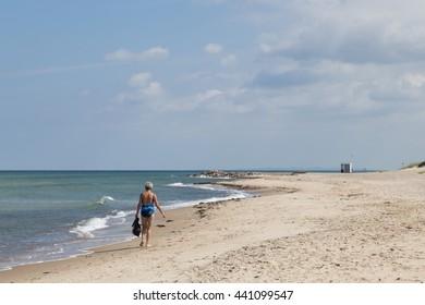Tisvilde, Denmark - June 20, 2016: An elderly lady walking on Tisvilde beach.