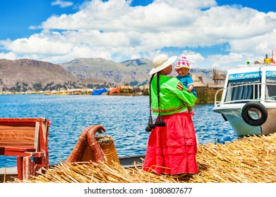 Titicaca lake, Puno, Peru - March, 20, 2017: Woman in traditional dresses with her child on Uros floating islands on Titicaca lake in Puno, Peru