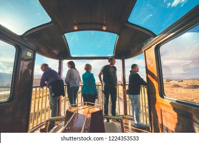 Titicaca Train, Peru - August 15th, 2018: Five tourists from different countries stand in the open-air observation car of Perurail Titicaca Train, and enjoy the beautiful view passing by.