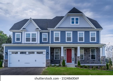 Title: Beautiful luxury American colonial traditional estate model home on a new development with two car garage, covered porch, blue horizontal vinyl lap siding, fiber cement shingle gable roof