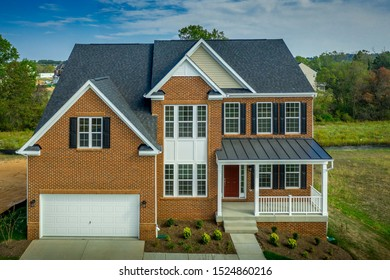 Title: Beautiful luxury American colonial traditional estate model home on a new development with two car garage, brick siding, fiber cement shingle gable roof , double hung windows with matching shut