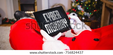 title for celebration of cyber monday against santa claus sitting and using digital tablet