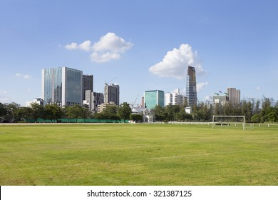 Title - Green field in the city Description - A football field with the blue sky in the city