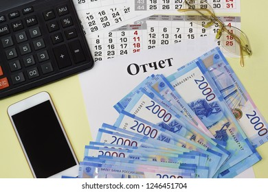 The title in the Russian language Report on a blank page, calculator, smartphone, sunglasses and a new Russian banknotes. The working place of the head