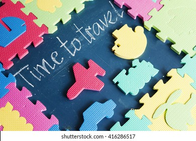 Title time to travel written in chalk on the blackboard in the composition with colorful puzzles